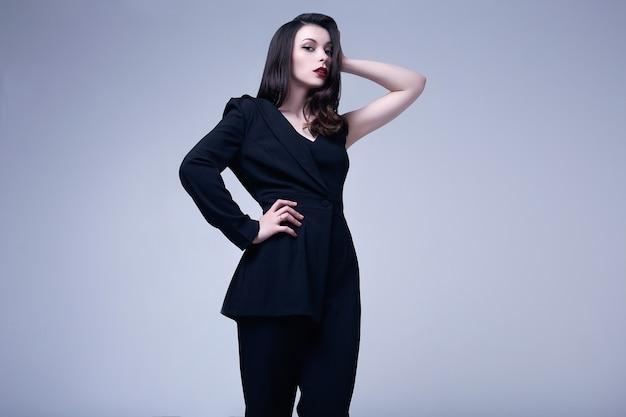 Elegante gotische brunettefrau mit den roten lippen im schwarzen anzug