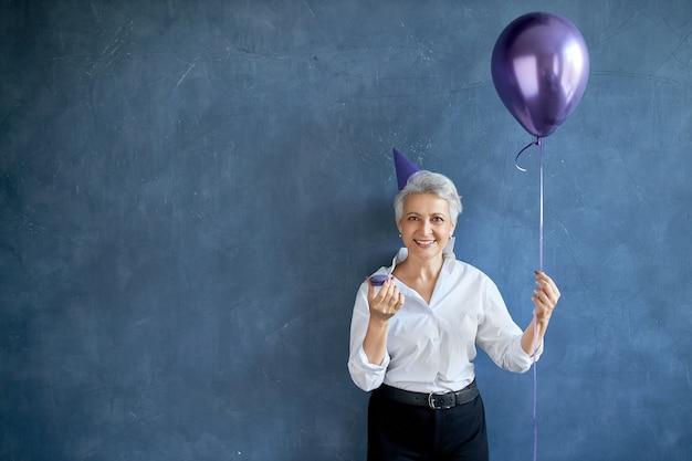 Elegante grauhaarige reife frau, die kegelhut und stilvolle kleidung trägt, die makrone auf der partei isst, luftballon hält