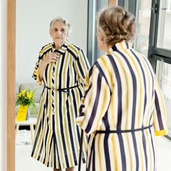 Elegante großmutter, die sich im spiegel ansieht