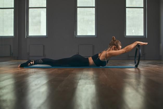 Elegante gymnastiklehrerin umgekehrte hände stützen körper auf boden und beine auf pilates-ring mit stretch-körper entwickeln weichheit im grauen wandhintergrundstudio.