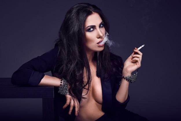 Elegante heiße brünette frau, die eine zigarette raucht