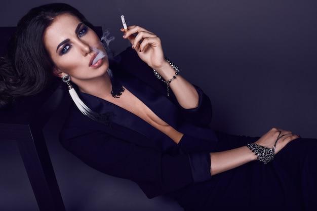 Elegante heiße brunettefrau, die eine zigarette raucht