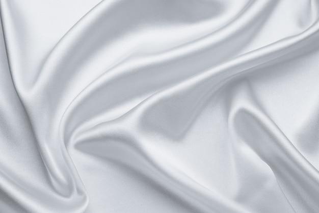 Elegante hellgraue stoffhintergründe. metallic graue farbe von glänzendem textil, weiche silberne textur. satinfalten, wellenmuster. luxusmode. glatte, glänzende kleidung. seidenbettlaken.