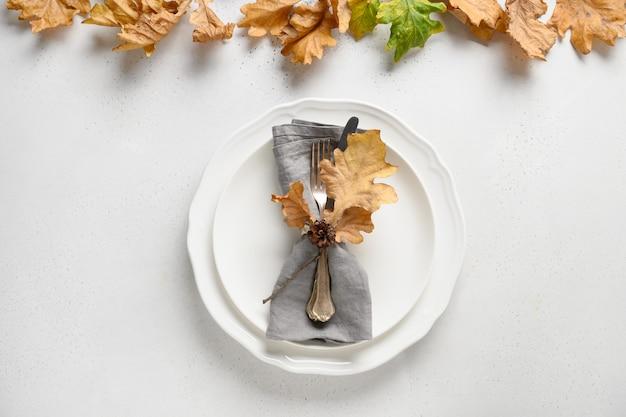 Elegante herbstgedeckung mit trockenen eichenblättern und weißem teller auf weißem tisch