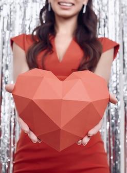 Elegante hispanische brunettefrau im luxuriösen roten kleid hält ein papierherz