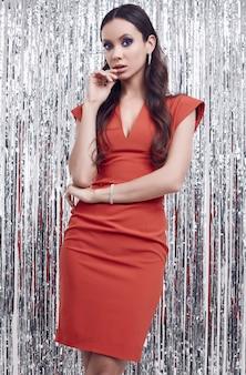 Elegante hispanische brunettefrau im luxuriösen roten kleid