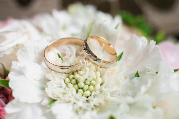 Elegante hochzeits-verlobungsringe auf weißen blumen