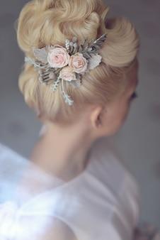 Elegante hochzeitsfrisur für das blonde blonde haar der braut mit zubehörhaarnadeln