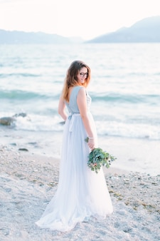 Elegante hübsche frau im luxuriösen blauen kleid, das den blumenstrauß in ihrer hand hält, steht am ufer des gardasees. lago di garda, italien