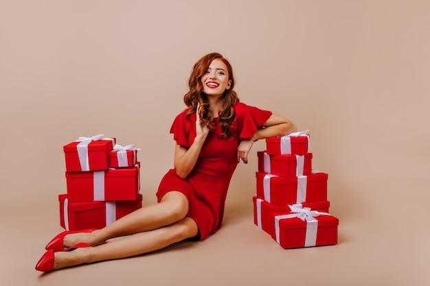 Elegante ingwerfrau in den hohen absatzschuhen, die an der weihnachtsfeier aufwerfen. innenfoto des reizenden lockigen mädchens im roten kleid, das spaß im geburtstag hat.