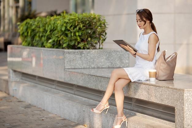 Elegante junge asiatin, die auf steinbank sitzt und tablette verwendet