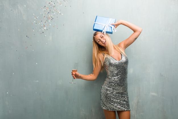 Elegante junge blonde frau, die neues jahr mit champagner, einem geschenk und konfetti feiert.