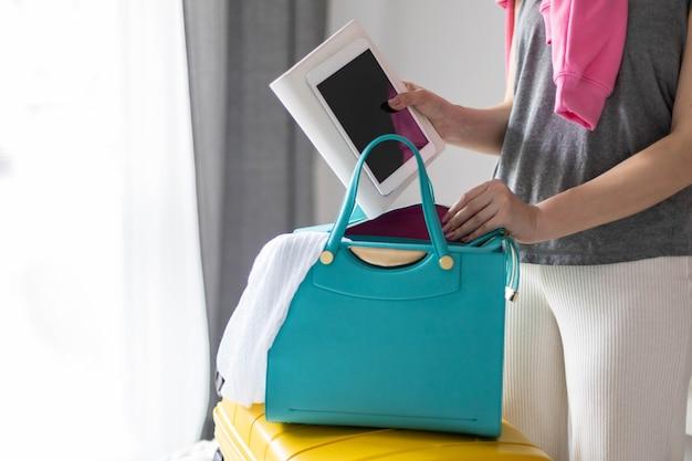 Elegante junge brünette frau, die tablet-pc und notizblock-tagebuch in die handtasche steckt, bereit zum reisen