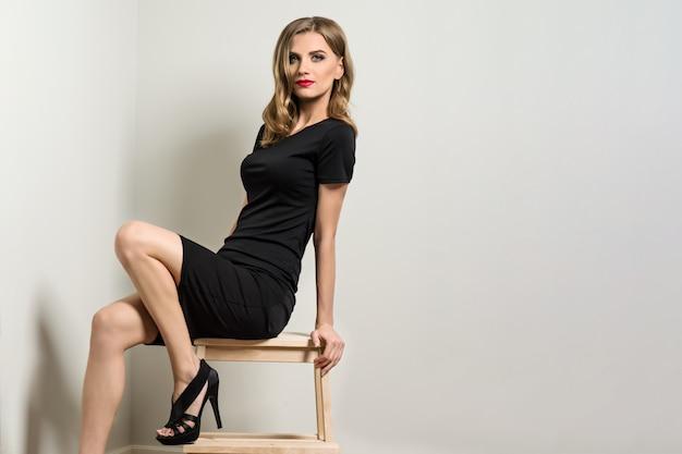 Elegante junge frau blond im schwarzen kleid