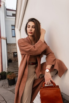 Elegante junge frau des modemodells in langem stilvollem mantel in beige modischer hose mit lederbrauner modischer handtasche in der nähe von weißem vintage-gebäude im freien. nettes städtisches mädchen, das draußen in der stadt aufwirft