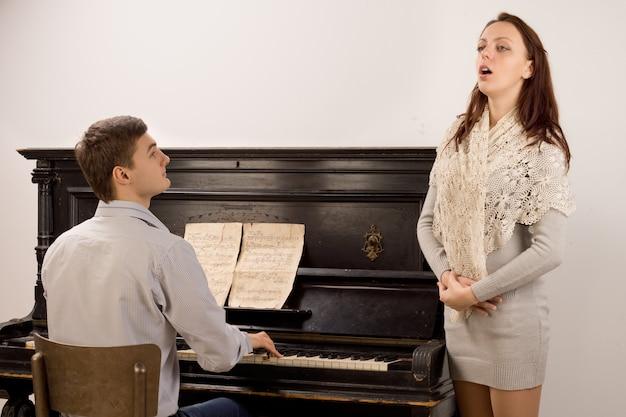 Elegante junge frau, die ein klassisches gesangskonzert gibt, das von einem gutaussehenden jungen mann auf einem klavier begleitet wird