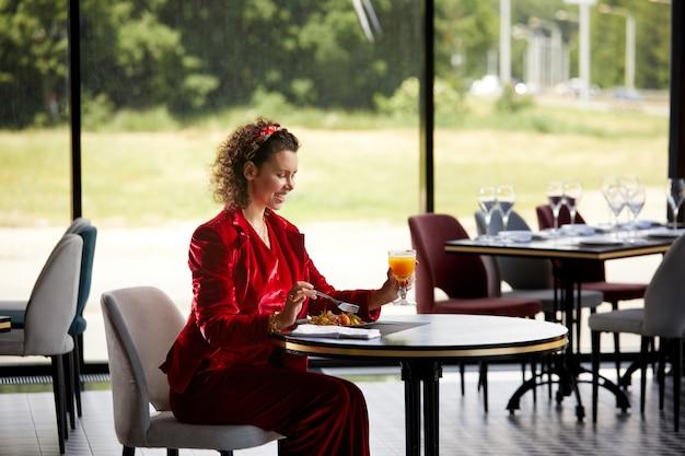Elegante junge frau, die garnelensalat zum mittagessen in einem gesunden lebensstil und einer diät des luxusrestaurants isst