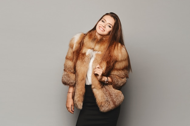 Elegante junge frau, die in einem luxusmodepelzmantel über hellgrauem hintergrund aufwirft, lokalisiert. winterkleidung.