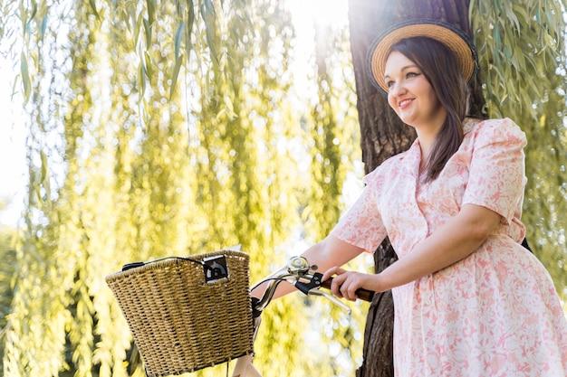 Elegante junge frau, die mit fahrrad aufwirft