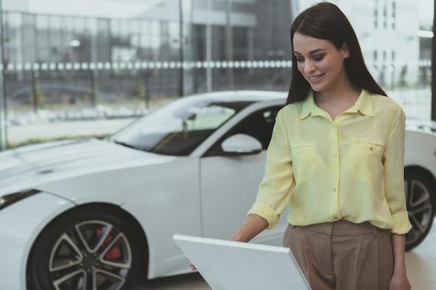 Elegante junge frau, die neues auto an der verkaufsstelle kauft