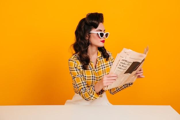 Elegante junge frau, die zeitung liest. studioaufnahme des konzentrierten pinup-mädchens, das auf gelbem hintergrund aufwirft.