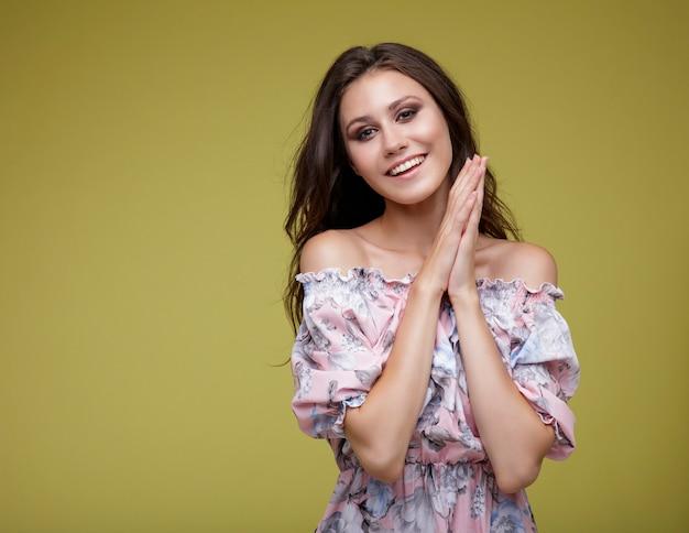 Elegante junge frau im kleid mit blumen auf zitronengelbem hintergrund modefoto studio shot