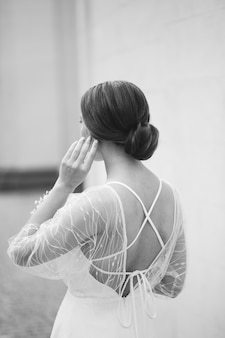 Elegante junge frau im modischen weißen kleid steht in der nähe der wand