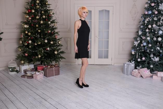 Elegante junge frau im schwarzen kleid nahe geschmücktem weihnachtsbaum