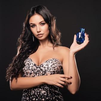 Elegante junge frau in einem schönen kleid mit parfüm o