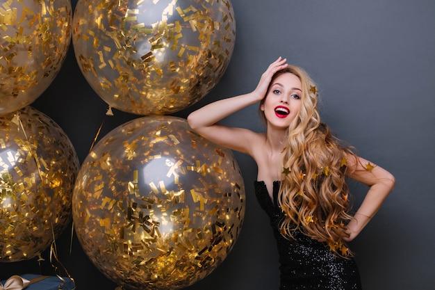 Elegante junge frau mit langen blonden haaren, die in der selbstbewussten pose auf neujahrsparty stehen. innenporträt des charmanten geburtstagskindes, das mit funkelnden luftballons aufwirft.
