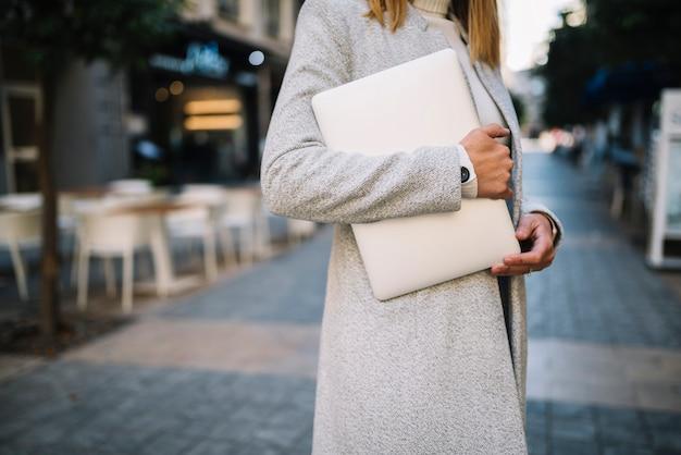 Elegante junge frau mit laptop auf der straße