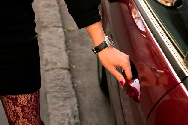 Elegante junge frau öffnet ihre autotür