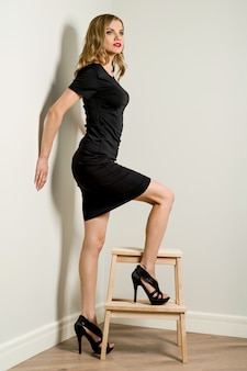 Elegante junge geschäftsfrau blond im schwarzen kleid