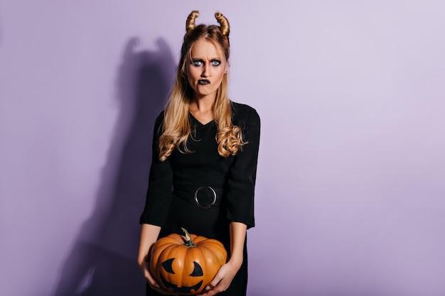 Elegante junge hexe, die halloween-kürbis hält. trauriges vampirmädchen mit dunklem make-up, das auf lila wand aufwirft.