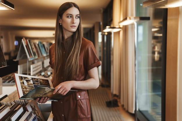 Elegante junge verführerische frau, die im vintage-buchladen einkauft, magazin hält, sich umdrehen blick außerhalb fenster.