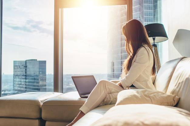 Elegante junge weibliche geschäftsfrau, die einen laptop verwendet, der zu hause auf einem sofa sitzt.