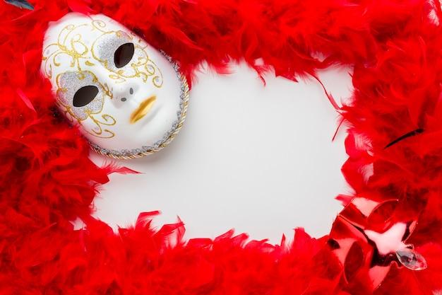 Elegante karnevalsmaske mit roten federn