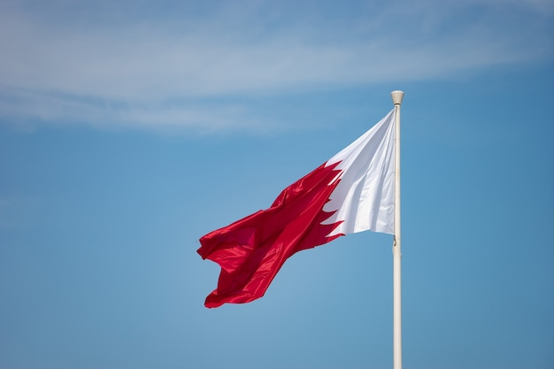 Elegante katar-flagge, die an einem hellen sonnigen tag in den himmel fliegt.