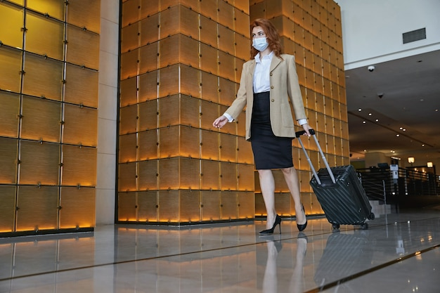 Elegante kaukasische dame, die einen kinderwagenkoffer trägt, während sie sich in einer hotelhalle mit einer medizinischen maske im gesicht befindet Premium Fotos