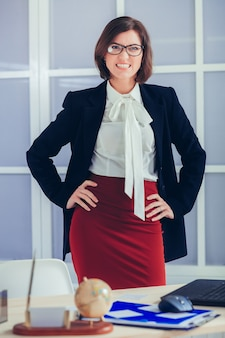 Elegante lächelnde geschäftsfrau in den gläsern im büro.