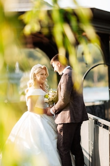 Elegante lockige braut und glücklicher bräutigam draußen auf dem hintergrund des sees. kreative stilvolle hochzeitszeremonie