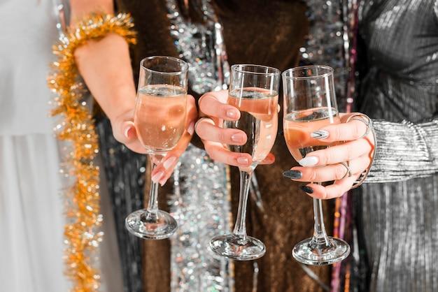 Elegante mädchen, die mit champagner anstoßen