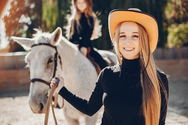 Elegante mädchen mit einem pferd in einer ranch