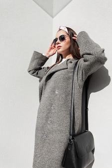 Elegante modische frau in vintage-sonnenbrille in stilvollem bandana in schönem grauem mantel mit schwarzer ledertasche genießt sonnenstrahlen in der nähe der wand. attraktives mädchenmode-modell in der jugendkleidung, die in der sonne aufwirft