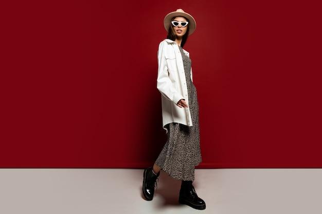 Elegante modische frau in weißer jacke und kleid posiert. stiefelette aus schwarzem leder. herbstkollektion. volle länge.
