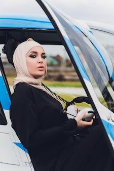 Elegante muslimische geschäftsfrau auf einem hubschrauber