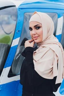 Elegante muslimische geschäftsfrau in der nähe des hubschraubers