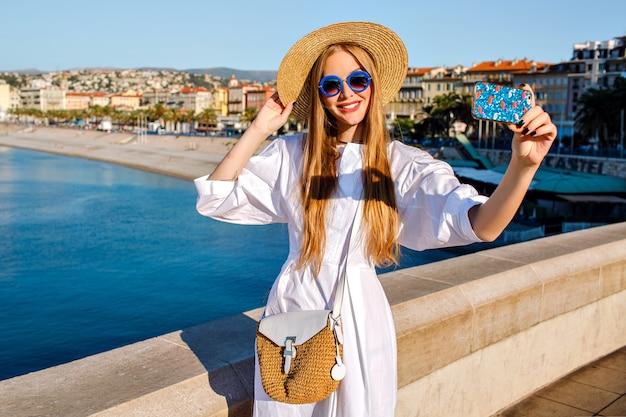 Elegante prächtige frau des glamours, die luxuriöses weißes kleid und strohaccessoires trägt, die selfie am strand machen