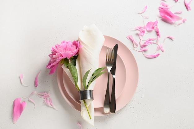 Elegante romantische tabelleneinstellung mit rosa pfingstrosenblumen auf einem weißen tisch.