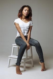 Elegante schöne afroamerikanerfrau, die in einem zeitgenössischen stuhl sitzt